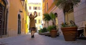 Steadicam and low angle shot of a woman walking along the narrow street with pad and making shots or video of buildings