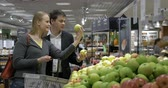smell : Young couple in the supermarket choosing and putting fresh apples into the shop basket.  They examining and smell the fruit to find the best Stock Footage
