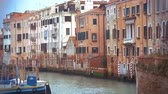 quiet : Slow motion of Venice canal with still water, old vintage style houses and moored boat. Classic Venetian cityscape Stock Footage