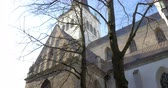 roof : Steadicam shot of a beautiful st. Olaf church in the old town of Tallinn, Estonia. View from below through the branches of a tree