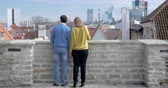 tallin : Steadicam shot of young loving couple having the date outdoor. They walking, looking at city panorama and then sitting on the bench holding hands