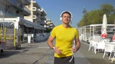fitness : Slow motion steadicam shot of a young smiling man in headphones with smartphone enjoying music while running in resort town in the morning. He passing by empty cafes and hotels Stock Footage