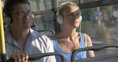 fone de ouvido : Young beautiful couple blond woman and man in glasses listening music in headset during bus trip against bus windows view Stock Footage