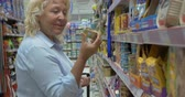 консервы : Senior blond woman in blue blouse is choosing canned pet food at supermarket with shop basket and reading ingredients on packages with smile big range of pet foods in aisle. Стоковые видеозаписи