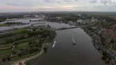 empty barge : Aerial panorama of town in Netherlands. Private houses, green areas and river with sailing barge Stock Footage
