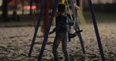 playground : Boy on the beach playground in late evening. He swinging empty swings