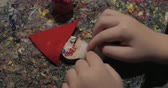サンタクロース : Close-up shot of a child finishing craftwork of Santa Claus. Arts and crafts devoted to Christmas