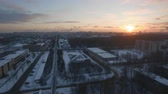 havasi levegő : Flying over winter city at sunrise, Russia. St. Petersburg view with houses, roads, bare trees and distant smoky pipes Stock mozgókép