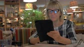 kaydırma : Senior woman in glasses spending leisure time in cafe and browsing web on digital tablet Stok Video