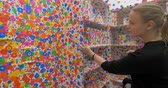 transformando : HELSINKI, FINLAND - JANUARY 07, 2017: Mother and son (with model release) visiting Obliteration Room. Viewers transforming space with colorful stickers. Exhibition of Yayoi Kusama. Helsinki Art Museum