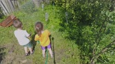 подруга : Two kids in the yard of countryside house. They help adults and watering plants with hose