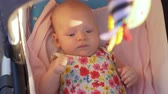 младенец : Quiet baby girl of three months lying in baby carriage with toy during summer outing