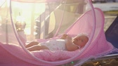 wach : Lovely baby girl lying in pink bassinet outdoor, she moving hands and legs. Shot against bright sunlight Stock Footage