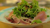 hams : Close-up shot of eating appetizer at the restaurant. Mix green salad with prosciutto