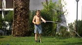 quintal : Boy struggling with water jet when watering the lawn in the garden near the house on hot summer day Stock Footage