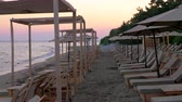 şezlong : Rows of empty sunbeds at the seaside. Scene of coastal resort at sunset Stok Video