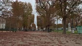 astarlı : PARIS, FRANCE - SEPTEMBER 29, 2017: Timelapse shot of walking along tree lined promenade and making the way to Palace in Luxembourg Gardens. Autumn scene with foliage on the ground Stok Video