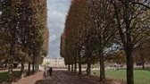 astarlı : PARIS, FRANCE - SEPTEMBER 29, 2017: Timelapse shot of walking in Luxembourg Gardens on autumn day. Moving along tree lined promenade to Palace Stok Video