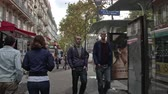 paryż : PARIS, FRANCE - SEPTEMBER 29, 2017: Timelapse shot of walking on roadside sidewalk in busy city street. Passing by cafes and stores