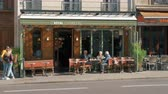 motorcyclists : PARIS, FRANCE - SEPTEMBER 29, 2017: Walking along Parisian street with few people relaxing in roadside cafes. Cyclists and motorcyclists passing by