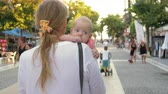 outing : Mum with baby having a walk outside on summer day. Woman carrying child in arms when wandering among the street vendors
