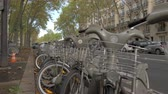 припаркован : Passing by the parking with rental bikes in the street of Paris. Easy and cheap way to travel in the city