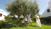four children : Cheerful family of four in the garden. Dad, son and mother with baby daughter in hands dancing and having fun near big olive tree