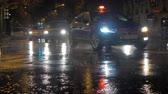 paryż : PARIS, FRANCE - SEPTEMBER 29, 2017: Slow motion shot of transport traffic in city street at night. Cars driving under pouring rain, beam from headlights reflecting on wet road and puddles