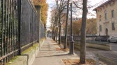 astarlı : Steadicam shot of walking along the tree-lined sidewalk in quiet street of autumn Paris. Yellow trees and foliage on the ground