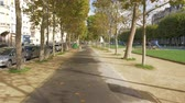 astarlı : PARIS, FRANCE - SEPTEMBER 29, 2017: Steadicam shot of walking on promenade lined with trees, dry leaves on the path. Autumn in the city