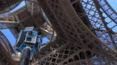 montáž : PARIS, FRANCE - SEPTEMBER 29, 2017: Low angle rotating shot of tripod with seven GoPro cameras shooting 360 Virtual reality video under the Eiffel Tower