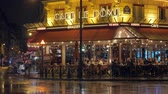 chovendo : PARIS, FRANCE - SEPTEMBER 29, 2017: Slow motion shot of people relaxing in outdoor terrace of Cafe Le Dome. View to the street in rainy evening, pedestrian sign blinking
