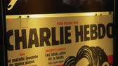 pubblicazione : PARIS, FRANCE - SEPTEMBER 29, 2017: Charlie Hebdo street banner displayed in night city. French satirical magazine, featuring cartoons, reports, polemics, and jokes Filmati Stock