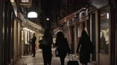 keskeny : VENICE, ITALY - APRIL 23, 2018: People walking along narrow paved street with stores and cafes at night Stock mozgókép