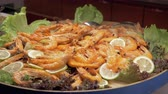 skrček : A closeup of a large dish full of cooked shrimps. It is decorated with lemon slices and lettuce leaves