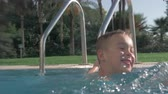 kaluž : Happy boy bathing in outdoor swimming pool and having fun with splashing water to the camera. Enjoyable summer day