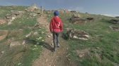 пеший туризм : Steadicam shot of the boy walking up the hill to see the ruins of ancient town Hierapolis. Tourism in Pamukkale, Turkey