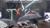 pessoa : A slow motion of a rain at an open air concert show. People with umbrellas are standing in front of the big stage, which is lightening with colorful illumination