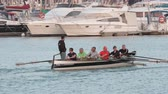cais : ALICANTE, SPAIN - APRIL 19, 2018: A group of man having training on rowing boat in city harbour, it sailing among the yachts Stock Footage