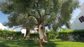 prole : Happy dad and son having fun and running around the big olive tree in the garden, following slow motion shot of father spinning child in hands