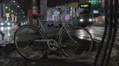 suja : HELSINKI, FINLAND - JANUARY 07, 2017: Night city street with people, cars and trams traffic, view to the abandoned bike near the post in dirty snow