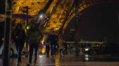 předpis : PARIS, FRANCE - SEPTEMBER 29, 2017: Slow motion shot of people walking across the road near illuminated Eiffel Tower at rainy autumn night