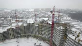 技術 : Drone view of tall cranes constructing modern apartment buildings on gray winter day