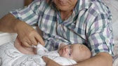 Medium shot of a grandfather holding newborn baby girl with a bottle on a pillow
