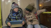 Medium shot of two young boys riding on a commuter bus during the evening in winter