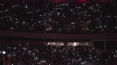 Wide shot of an large audience inside an arena with their cellphone screen on in time with the music