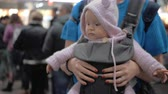 Medium panoramic handheld shot of a cute baby in a baby carrier while waiting with her mother to travel in the airport terminal