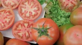 Ripe sliced and whole tomatoes lying on leaves of fresh lettuce on table Stock Footage