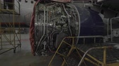 técnico : Jet engine under going repairs inside an airplane hanger