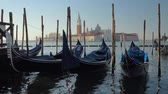 benátky : Wide slow motion shot of gondola boats in Venice Italy with a church in the distance